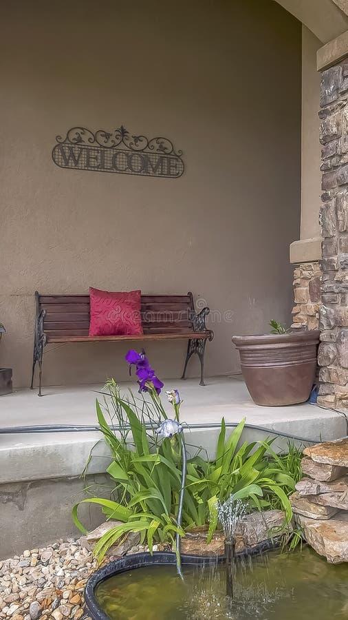 Det vertikala den dekorativa trädgårddammet och lilla springbrunnen som omges av växter och, vaggar arkivbilder