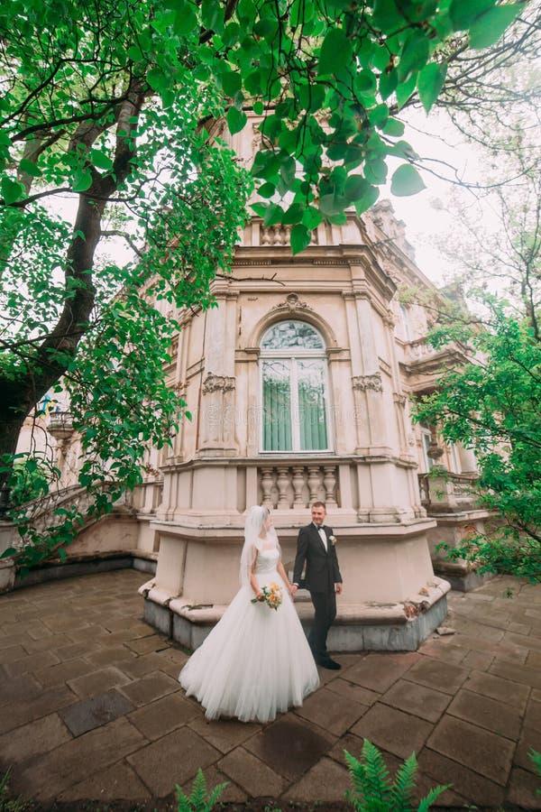 Det vertikala fotoet av de gå nygifta personerna nära den gamla byggnaden som omges av träd royaltyfri bild