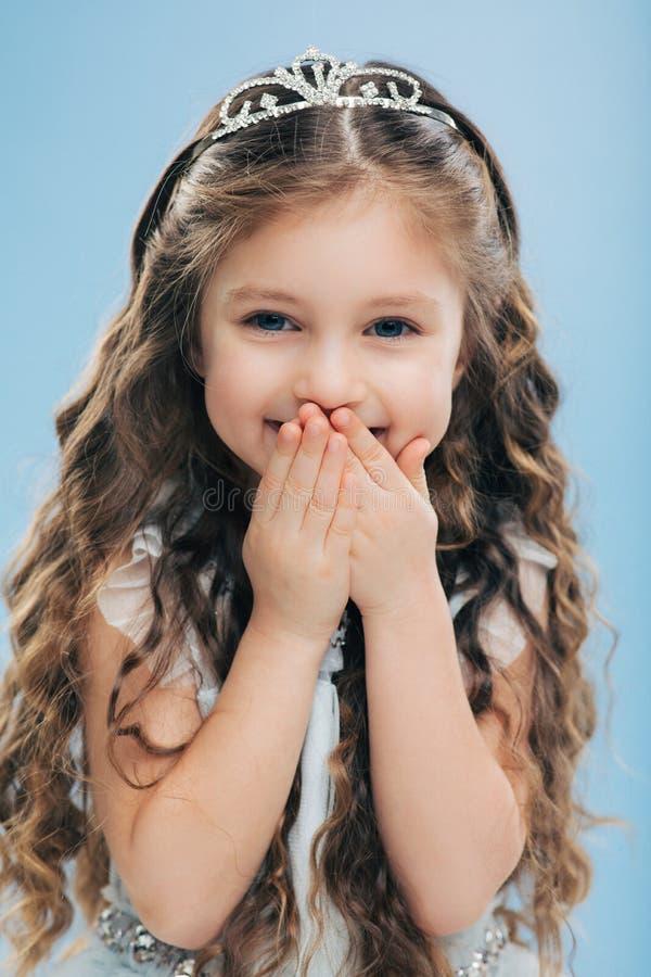 Det vertikala skottet av det positiva småbarnet täcker munnen med händer, fniss positivt, bär kronan, uttrycker lycka, över royaltyfri bild