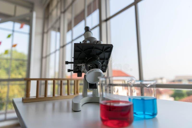 Det vetenskapliga mikroskopet för att testa med laboratoriumglasföremålet på den vita tabellen royaltyfri foto