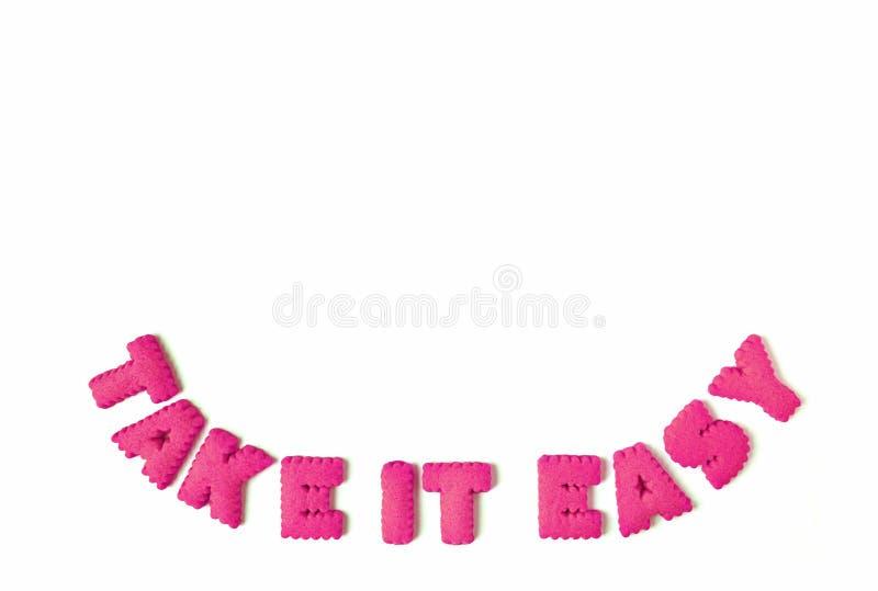 Det vibrerande rosa alfabetet formade kakor som stavar ordet, TAR DET som VAR LÄTT på vit bakgrund arkivfoto