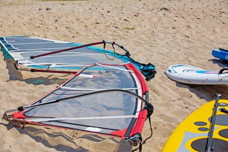 Det vindsurfa brädet med seglar att ligga på sanden arkivfoto