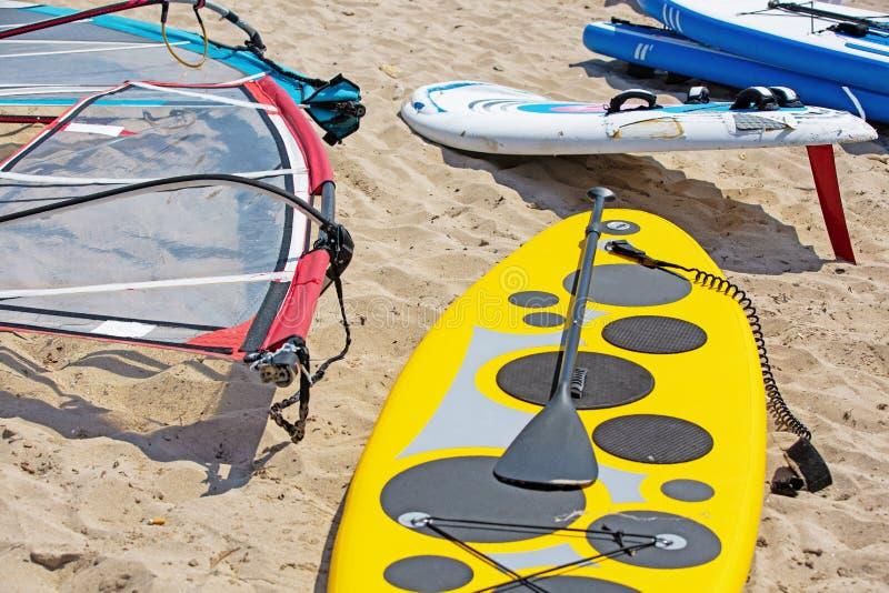 Det vindsurfa brädet med seglar att ligga på sanden royaltyfria bilder