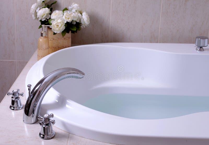 Det vita badet badar med vattenkranen och mozaic tegelplattor arkivbild