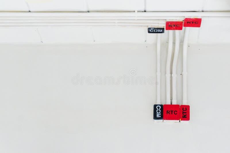 Det vita elektriska PVC-r?ret i r?tt och svart f?rbinds till kraftledningar eller elektriska tr?dar, EthernetUTP kablar, internet royaltyfri bild