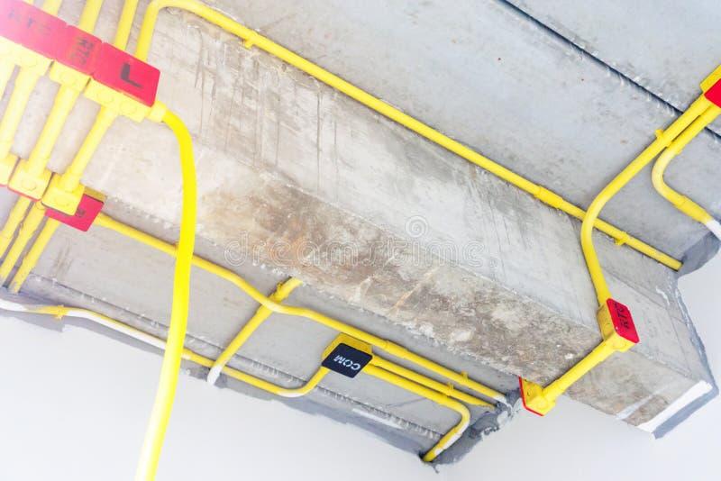 Det vita elektriska PVC-r?ret i r?tt och svart f?rbinds till kraftledningar eller elektriska tr?dar, EthernetUTP kablar, internet royaltyfria bilder