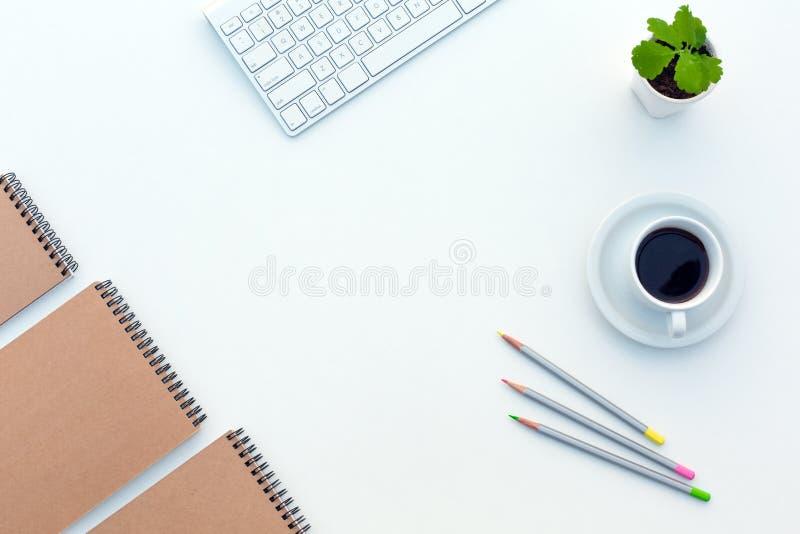 Det vita funktionsdugliga skrivbordet med affärsobjektkaffe och skissar böcker arkivbilder
