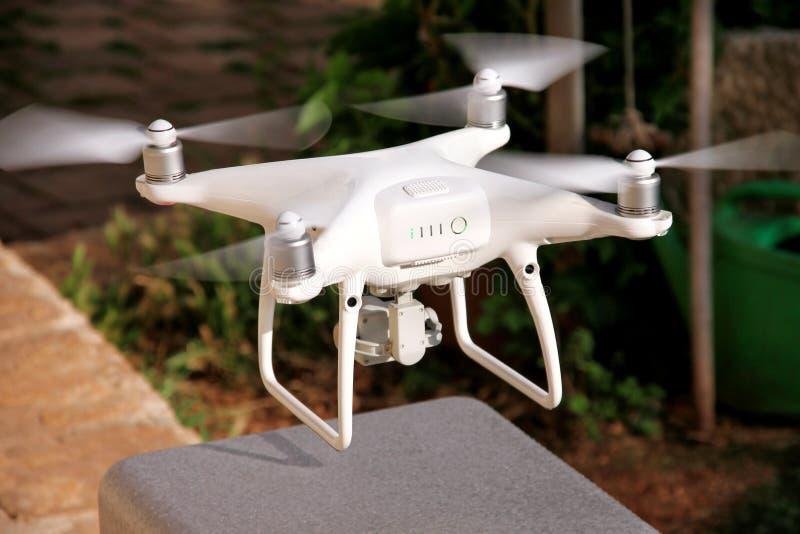 Det vita kvadrathelikoptersurret med den digitala kameran 4K är tar av och att flyga högt i luft, att ta foto och rekord- längd i royaltyfri fotografi