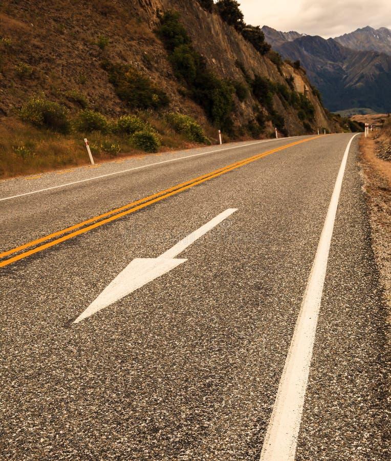 Det vita piltrafiktecknet, gula delande linjer och den vita vandringsledet fodrar på den lantliga vägen för asfalt royaltyfri bild