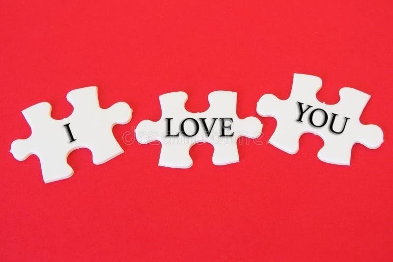 Det vita pusslet med ett skriftligt ord älskar jag dig på en röd bakgrund arkivfoto