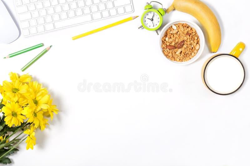 Det vita skrivbordet med tangentbordet, musen, färgrik brevpapper, gulingblommor, plattan med granola, bananen och den stora kopp royaltyfria bilder