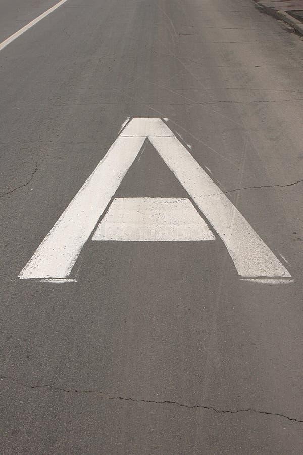 """Det vita tecknet på en för väg""""Buslane†i form av en stor versal A arkivbild"""