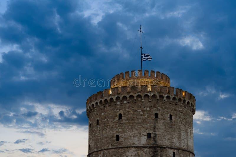 Det vita tornet av Thessaloniki, Grekland med att vinka den grekiska flaggan överst fotografering för bildbyråer