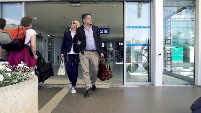 Det vuxna paret som lämnar flygplatsen, folket som ankommer på semester, familj semestrar royaltyfria foton