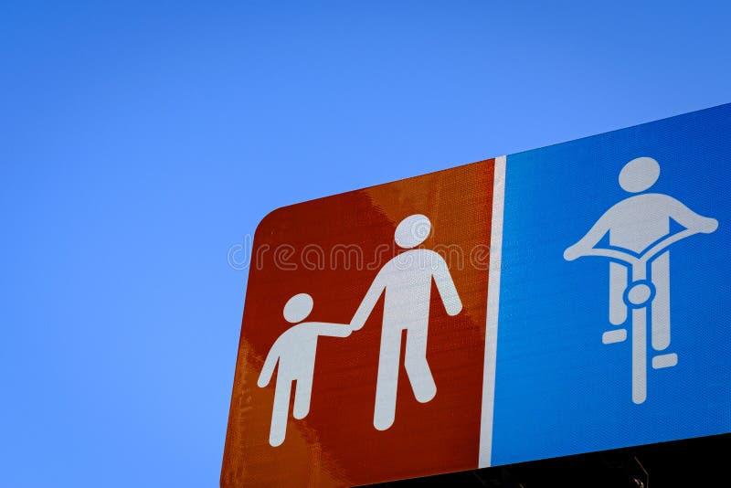 Det vuxna symbolet går handen av barn skylt och cykelgrändskylten med bakgrunder för blå himmel royaltyfria bilder