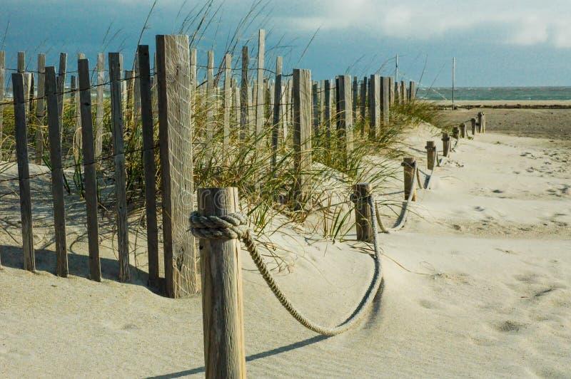 Det Wood staketet och repet fäktar på stranden med sand- och platshavre royaltyfri foto
