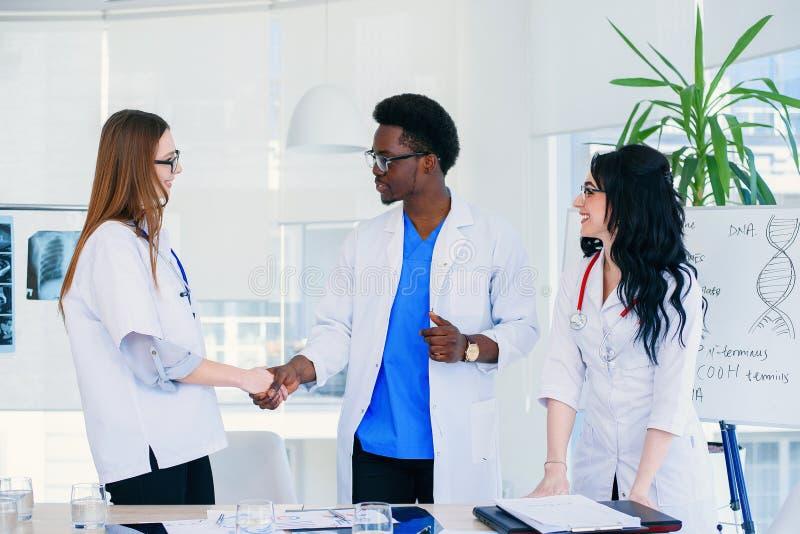 Det yrkesmässiga laget av en man och två kvinnliga doktorer nådde ett gemensamt beslut för att diagnostisera patienten H?lsov?rd  royaltyfri fotografi