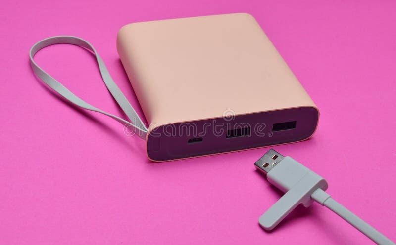 Det yttre batteriet för laddande smartphones och grejer med en usb kablar närbild på en rosa bakgrund Maktbank arkivbild