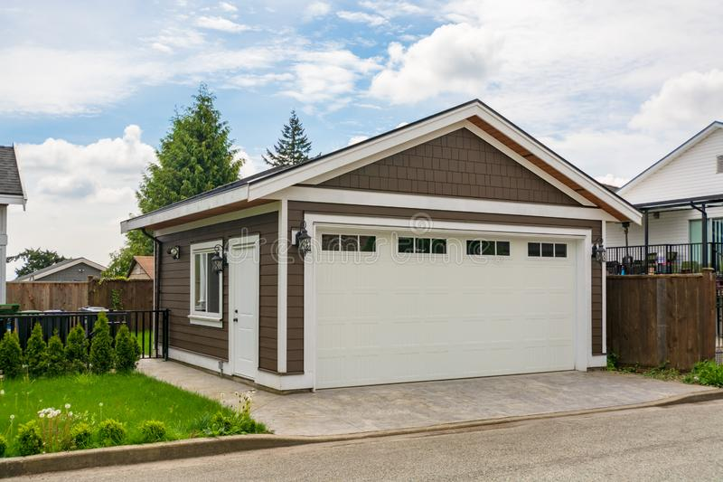 Detached garage of residential house with asphalt road in front. stock photos