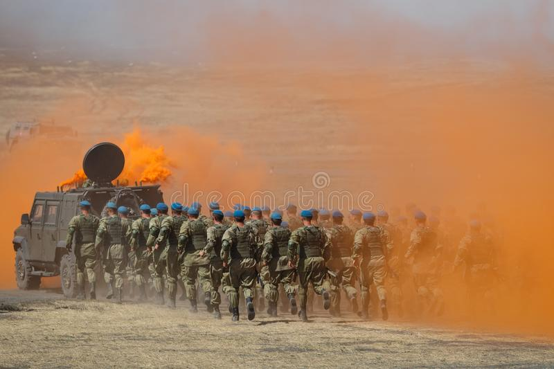 Detachment of Russian paratroopers runs for an armored car across the field in protective orange smoke stock photography