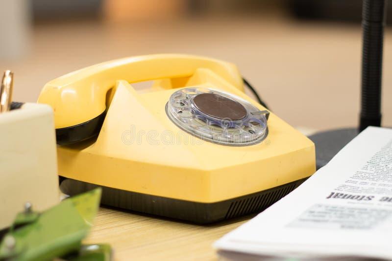 Detail über ein altes gelbes Retro- Telefon auf einem Weinleseschreibtisch in 80s lizenzfreie stockfotografie