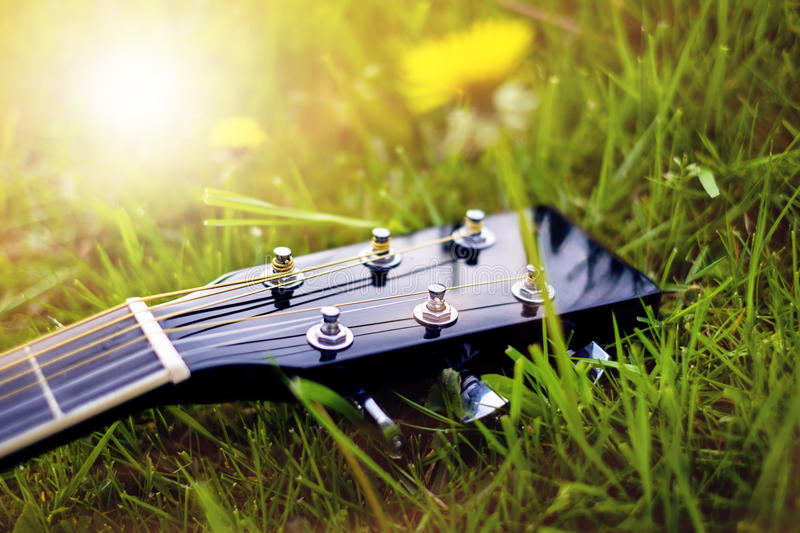 Detail of acoustic guitar on a grass. Natural background with flowers, grass and sun. Musical instrument. royalty free stock photography