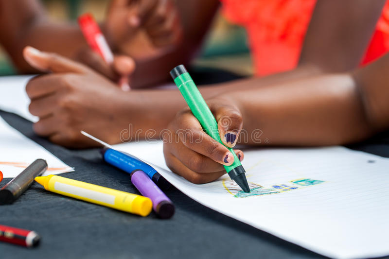Detail of African kids hands drawing. royalty free stock image