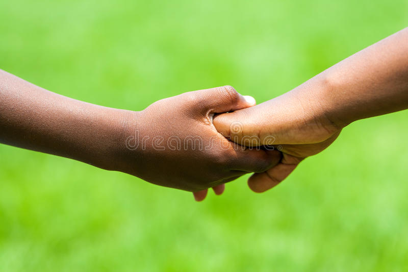 Detail of African kids holding hands. royalty free stock image