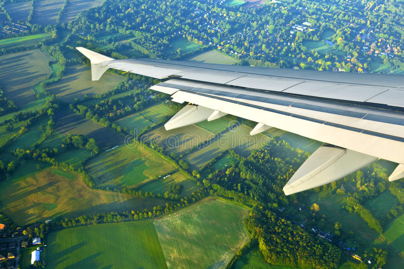 Detail of aircraft wing. With fields stock photos