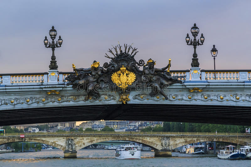Detail of Alexander III bridge. PARIS, FRANCE - May 15, 2015: This is gilded coat of arms of the Russian Empire in the middle of the sculptural decoration of the stock photography