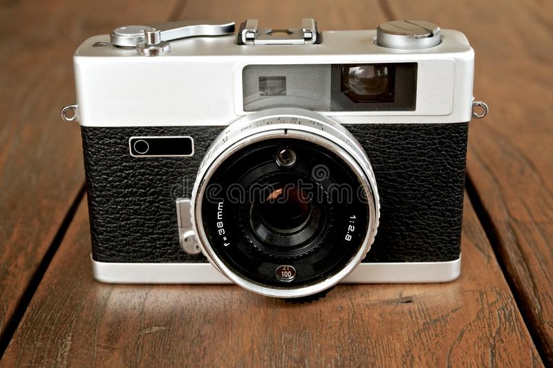 Detail of analog camera. Analog camera with wooden background royalty free stock photo
