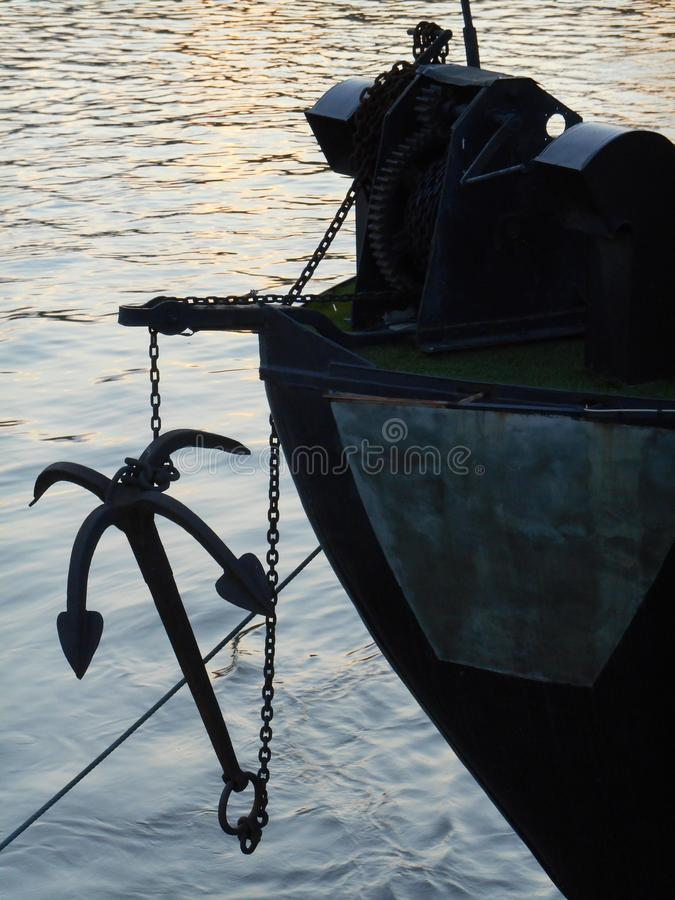 Anchor on boat at nightfall. Detail of anchor with chain on river boat, boat in the dock, closeup royalty free stock image