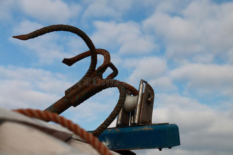 Detail of an anchor of a fishing boat. And the background sky stock image