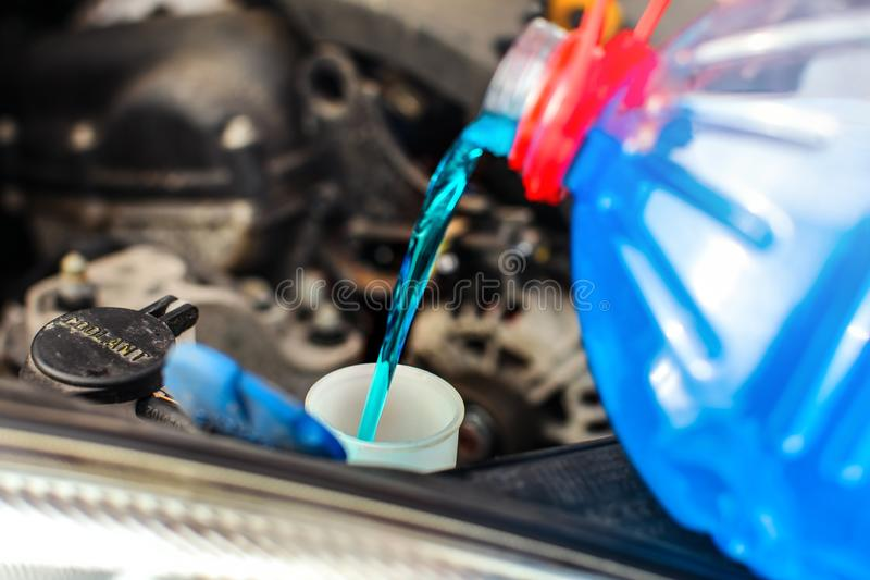 Detail on antifreeze car screen wash liquid pouring. Into dirty car from blue and red anti freeze water container royalty free stock image