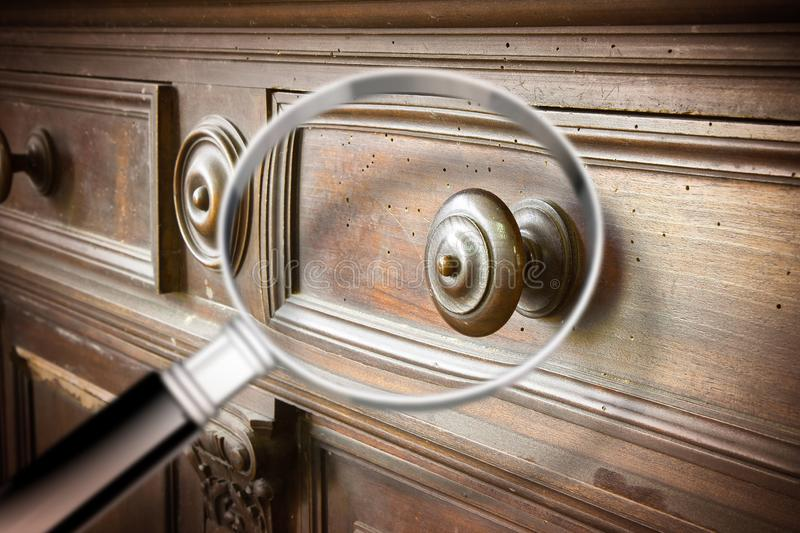 Detail of an antique wooden italian furniture just restored with a magnifying glass on foreground looking for woodworm threat stock photos