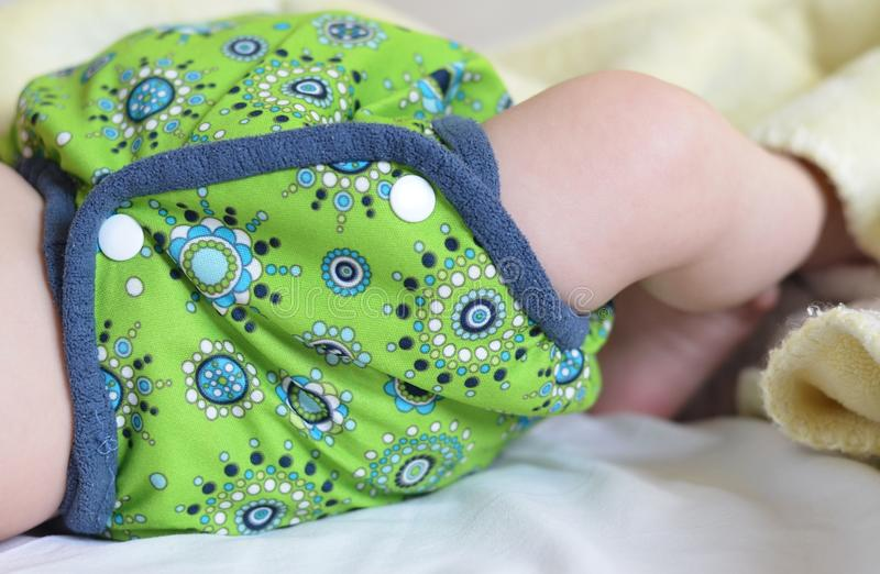 Detail of baby´s hip dressed in green cloth diaper. Detail of cloth diaper closing on patents royalty free stock photos