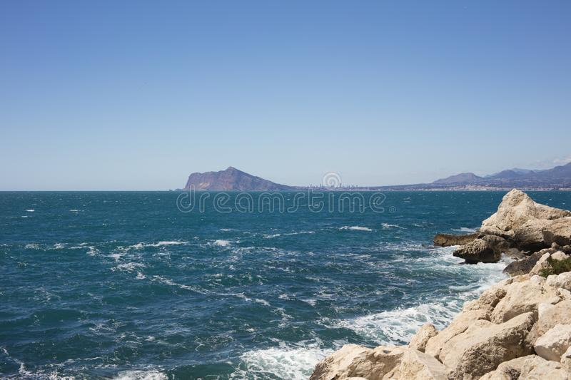 Detail of beach with turquoise and blue sea with Altea and Benidorm in background stock images