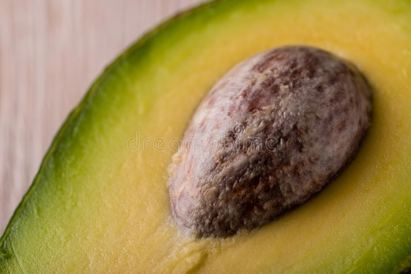 Detail of big avocado core in half of fruit. Horizontal photo with detail of big brown avocado core still placed in half of green yellow fruit. Light wooden royalty free stock image