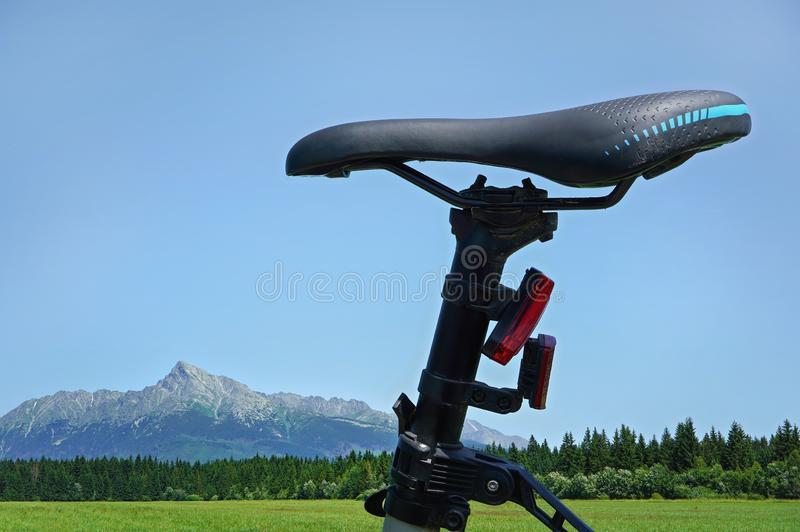 Detail on bike saddle, with green meadow and mountains mount Krivan in background - cycling in country concept.  royalty free stock photo
