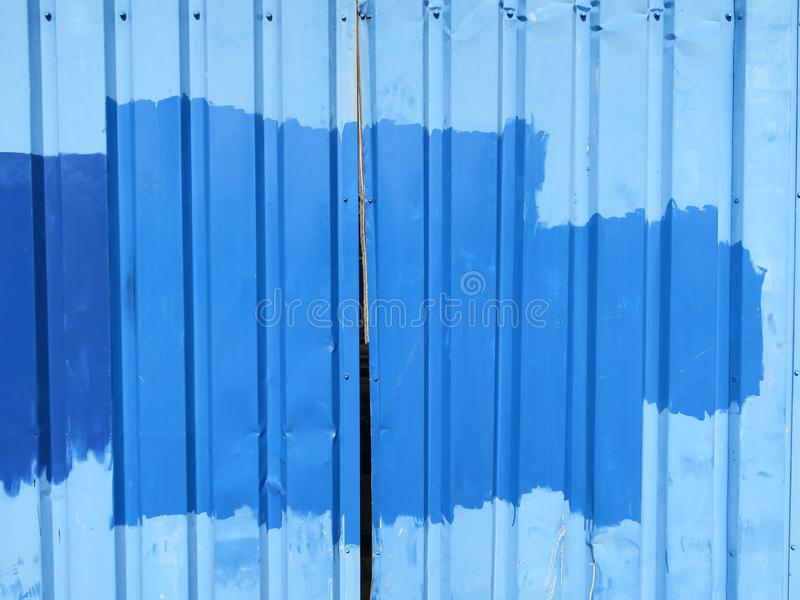Detail of a blue painted metal doors of an old shack or barn. A detail of a blue painted metal doors of an old shack or barn stock image