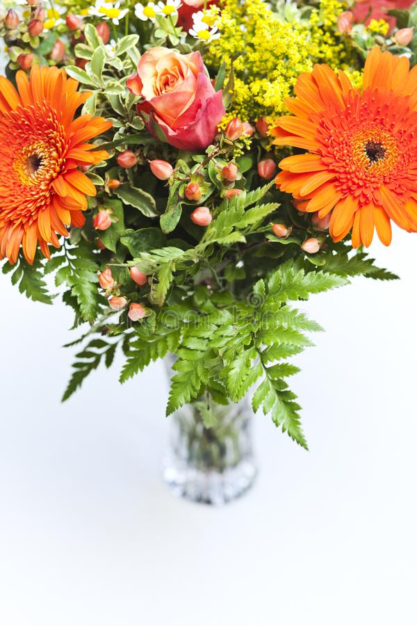 Detail of a bouquet of orange, yellow and red flowers in a vase. stock photography