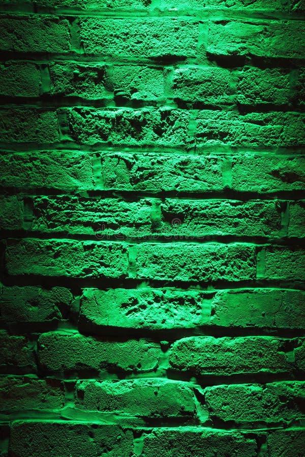 Green illuminated brick wall for Background stock photos