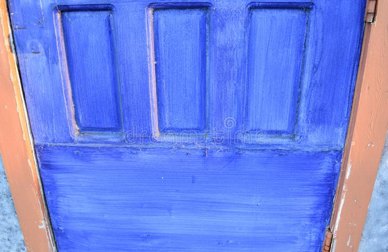 Detail of a bright blue door. Blue door in a terra cotta color building in cloudy morning light royalty free stock photo