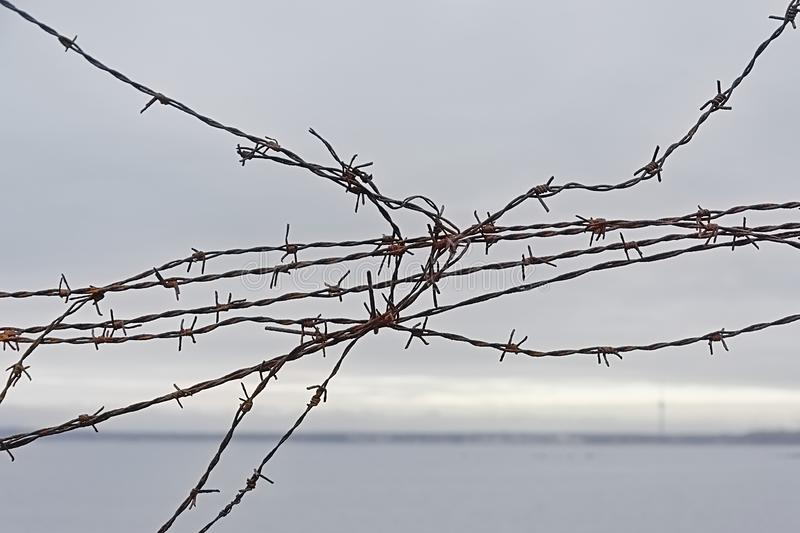 Detail of a broken fence with barbed wire, with sea and coast in the background royalty free stock image