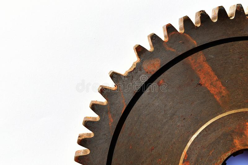 Broken old and rusty gear on white paper background stock image
