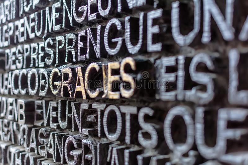 Detail of the bronze door of Passion facade of Sagrada Familia. Detail with word Gracies Thanks in catalan on the bronze door of Passion facade of Sagrada stock photography