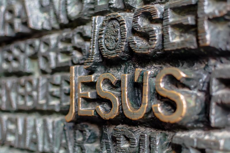 Detail of the bronze door of Passion facade of Sagrada Familia. Detail with word Jesus on the bronze door of Passion facade of Sagrada Familia in Barcelona. The royalty free stock photography