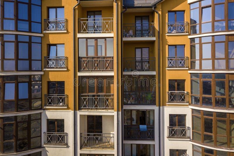 Detail buitenmuur van flat of bureau de bouw Gesmeed balkontraliewerk, blauwe die hemel in glanzende spiegelvensters wordt weersp stock afbeelding