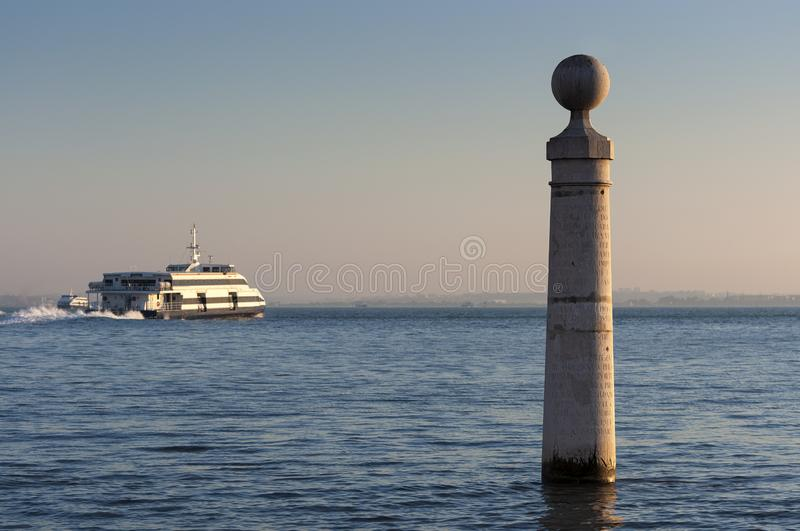 Detail of the Cais das Colunas in the city of Lisbon, Portugal. With a passenger boat on the Tagus River Rio Tejo on the background royalty free stock image