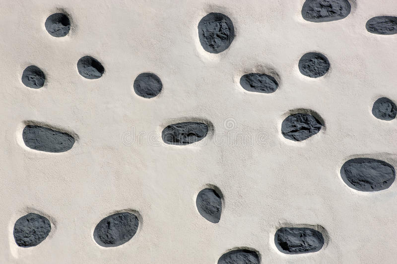 Detail of a Canarian exterior wall. In which the dark natural stones except a few specimens were covered with white plaster. Taken in La Gomera, Canary Islands stock photo